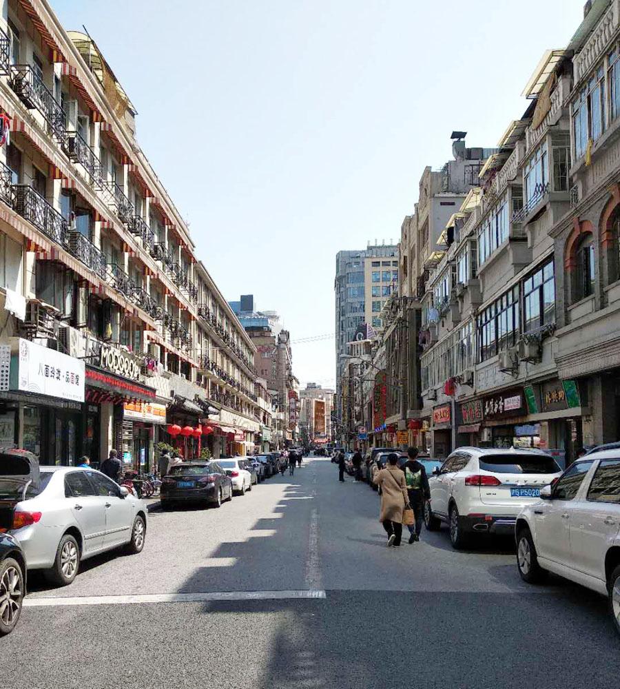 autoluwe winkelstraat in Shanghai, nu met geparkeerde auto's