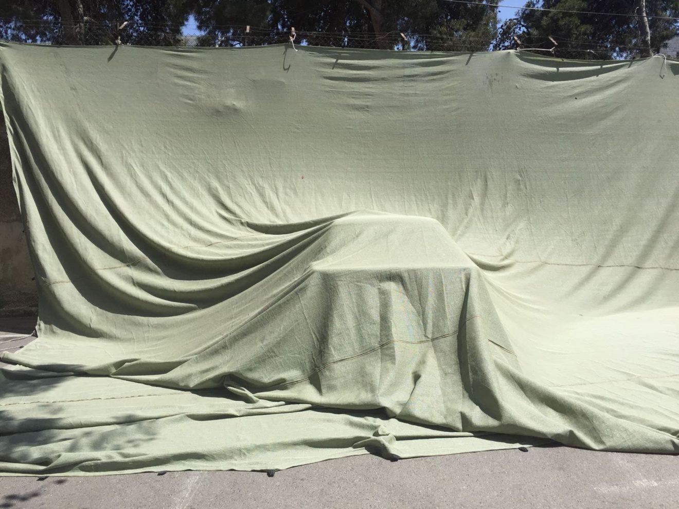 een scherm van doek dat een naar voren geschoven voorwerp bedekt