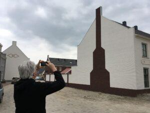 De onderzoeker fotografeert een verwijzing naar een historische schoorsteen aan een van de bijgebouwen van Het Landgoed in Almere-Nobelhorst
